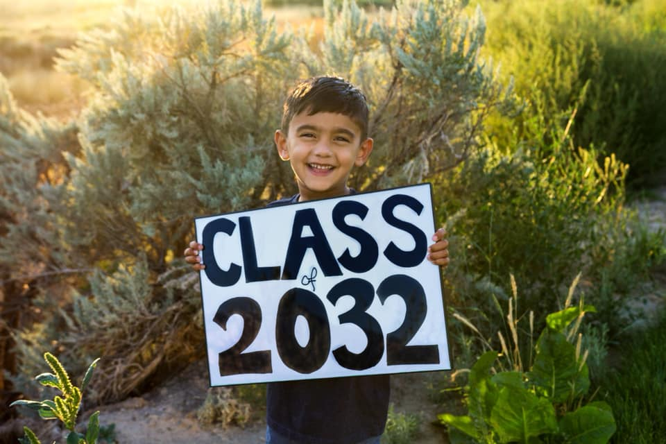 "Photo of a smiling little boy standing in front of greenery holding a handmade ""Class of 2032"" sign."