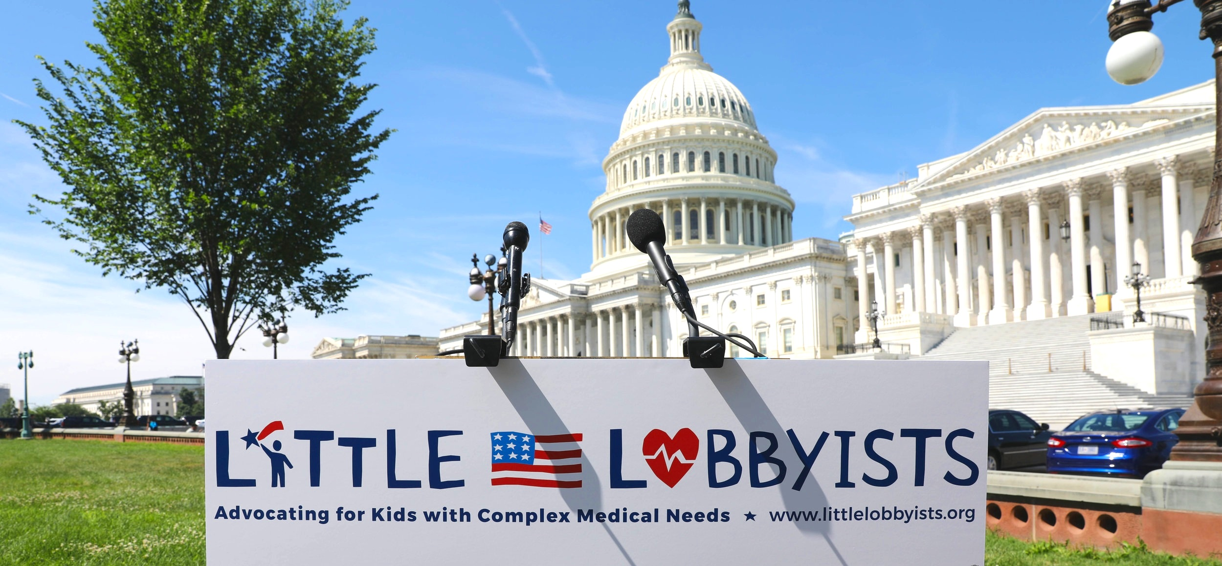 Podium with Little Lobbyists logo in front of the U.S. Capitol