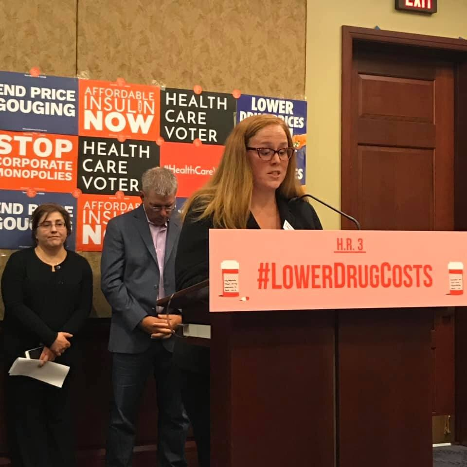 [image description: Little Lobbyists mom and director of operations, Tasha Nelson, speaking at the podium of a press conference for affordable pharmaceuticals.]