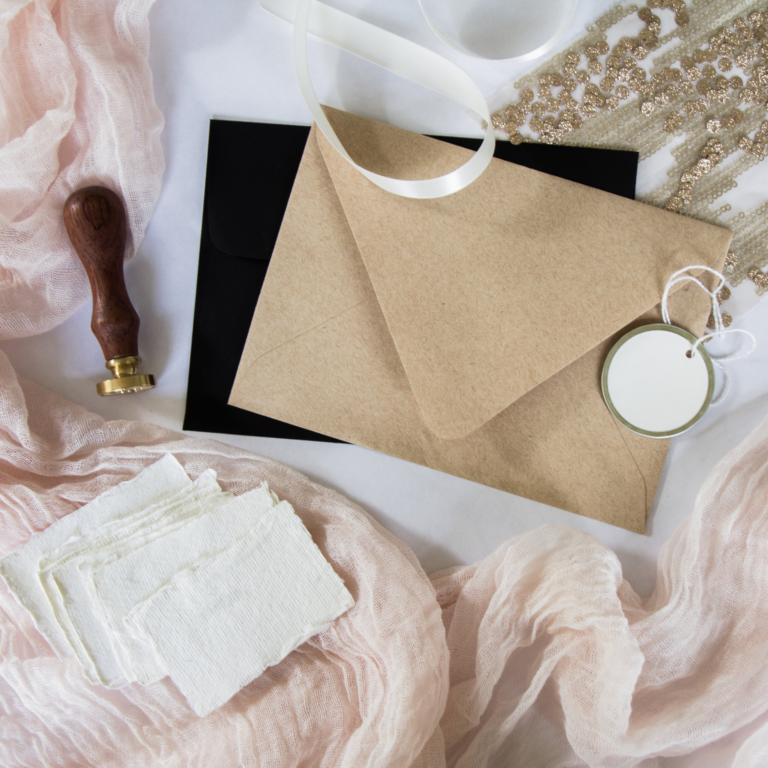 Blush pink cheesecloth with kraft paper A7 envelope, black invitation envelope, round hang tag, wax seal, deckled place card.