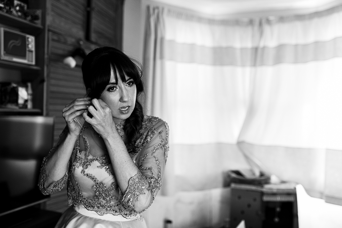 Bride putting on her earrings Sophie Lake Wedding Photography
