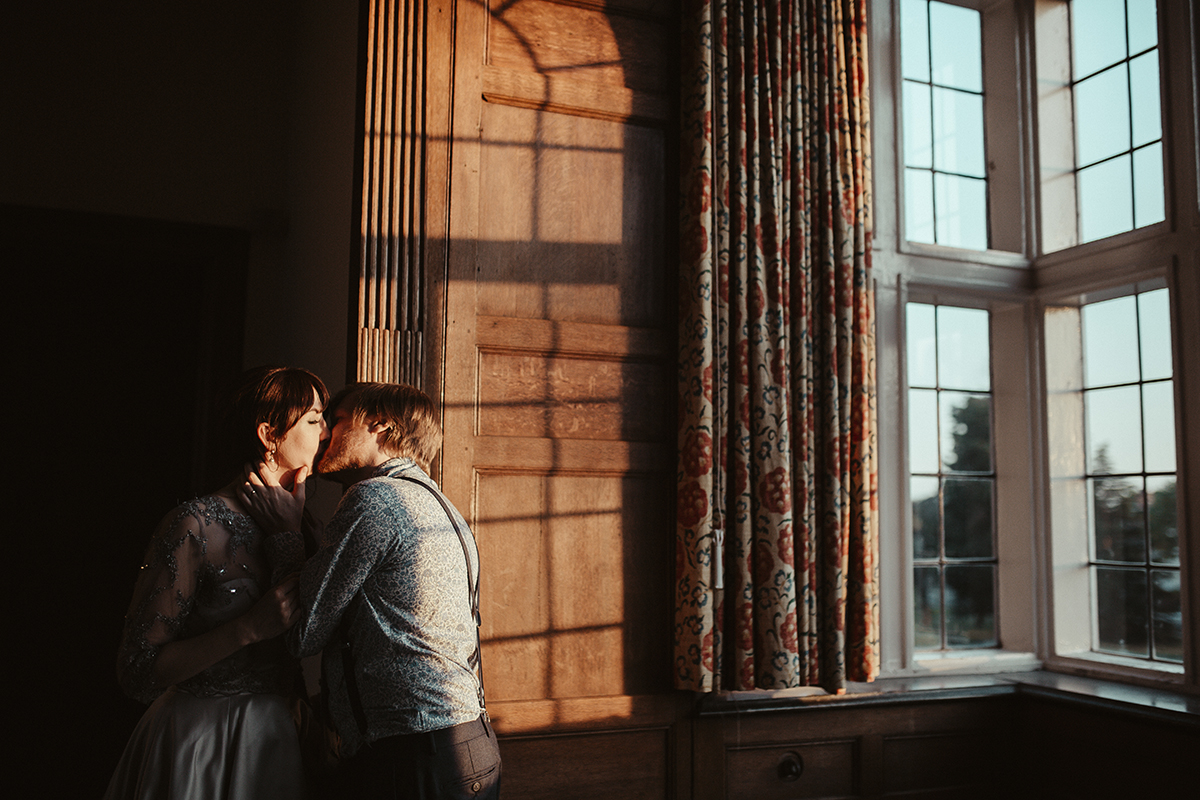 Bride and Groom kissing near window Sophie Lake Photography