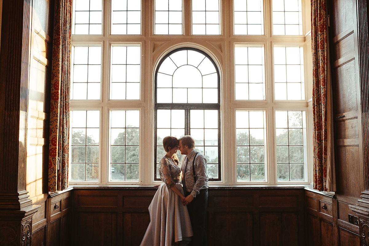 Bride and Groom standing by window Sophie Lake Photography