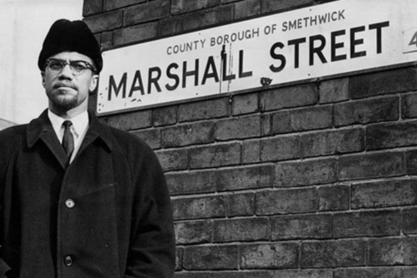 Feb 1965: Malcolm X visited Marshall Street in Smethwick on the invitation of IWA (GB). Peter Griffiths (Tory MP) won an election in Smethwick on the promise that the government would purchase any house that went on sale to keep them from being purchased by people of colour. Image:    Socialist Worker