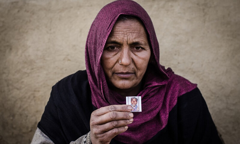 Banu Begum holding a picture of her husband who disappeared 20 years ago when he was out shopping for their daughter's wedding. APDP has estimated that 8,000-10,000 men have disappeared since 1989. Image:    Dawn