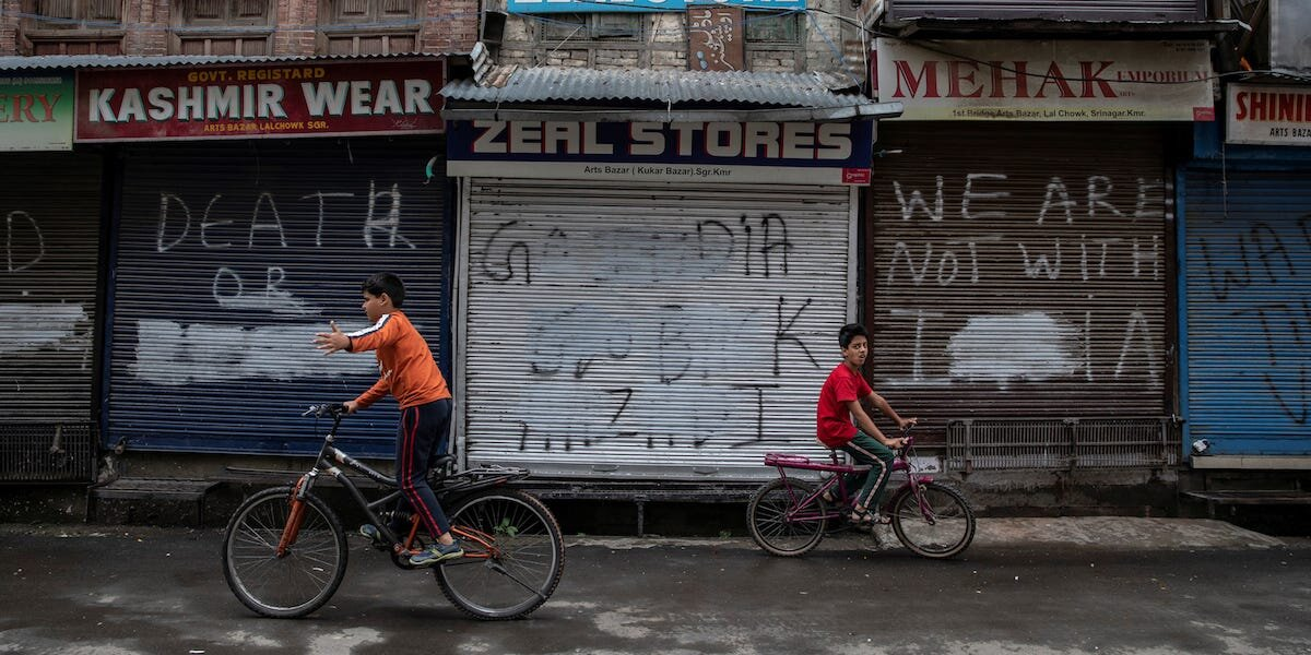 Aug 14, 2019: Two Kashmiri boys ride their bicycles besides closed shops on an empty street in Srinagar. Image:    Danish Siddiqui/Reuters