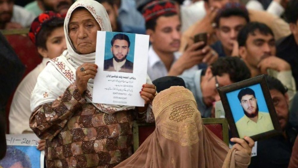 "Women hold images of their loved ones who have gone missing during the conflict in Northwest Pakistan. One of PTM's demands is that ""missing persons"" be presented in the courts and be granted the right to a fair trial. Image:    France 24"