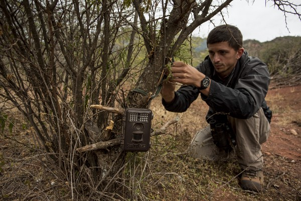Chris Jordan sets a camera trap by the side of a trail