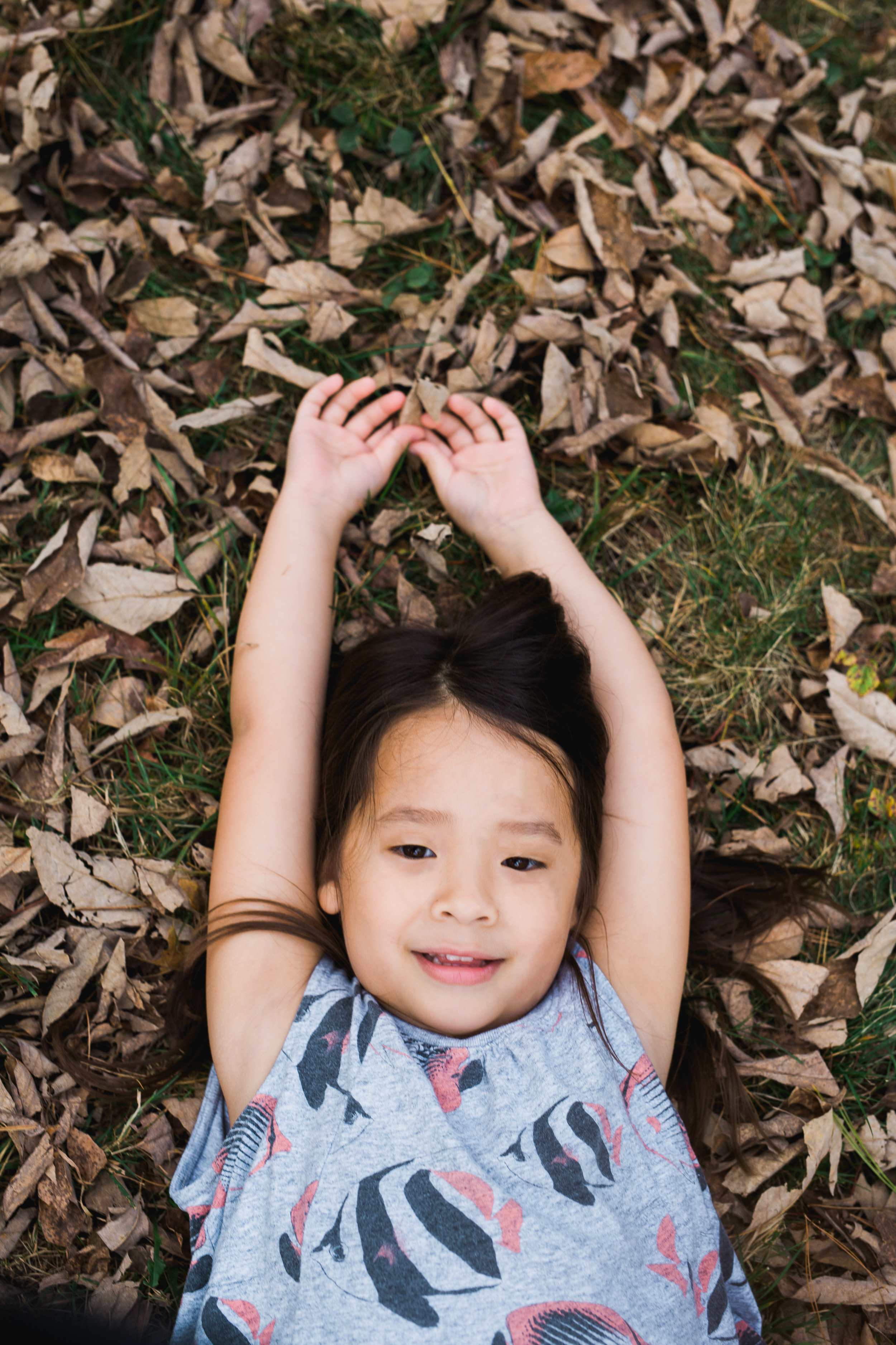 Greater Boston family photographer Joy Uyeno Sudbury little girl in the fall leaves