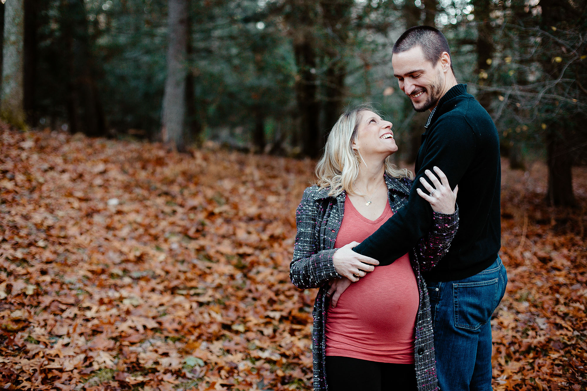 Greater Boston family photographer Joy Uyeno Sudbury husband and pregnant wife in back yard woods