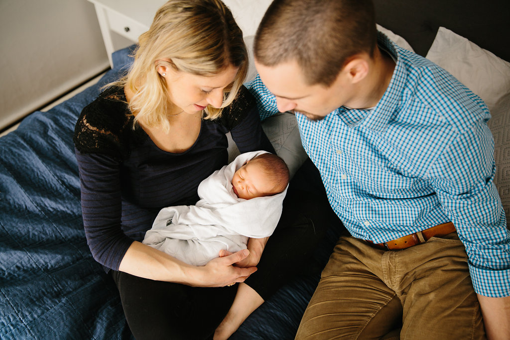 Parents and newborn baby girl during photo session at home