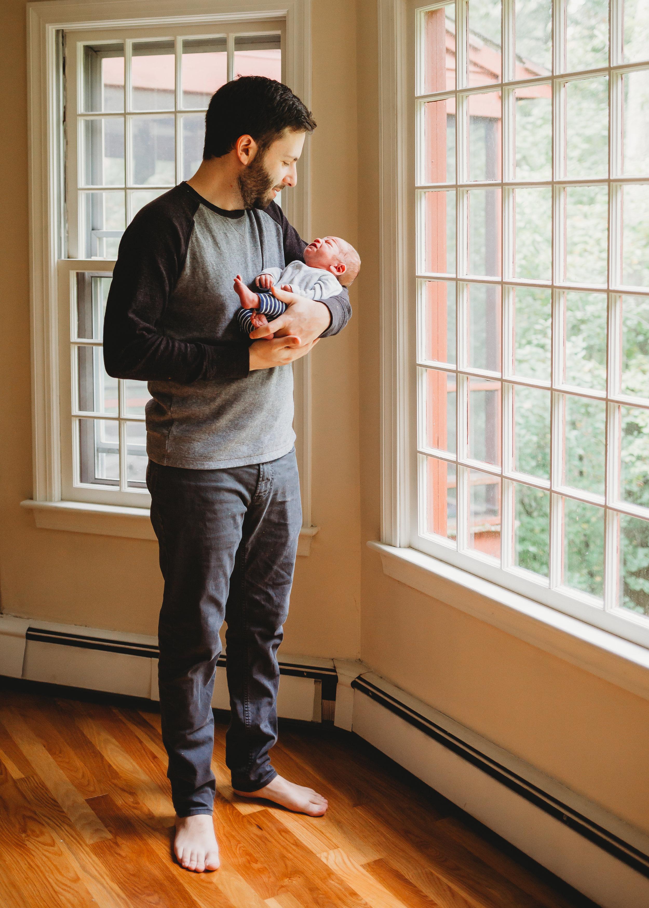 Dad holding newborn near windows. Sudbury newborn photography / Boston family photographer / natural light / lifestyle