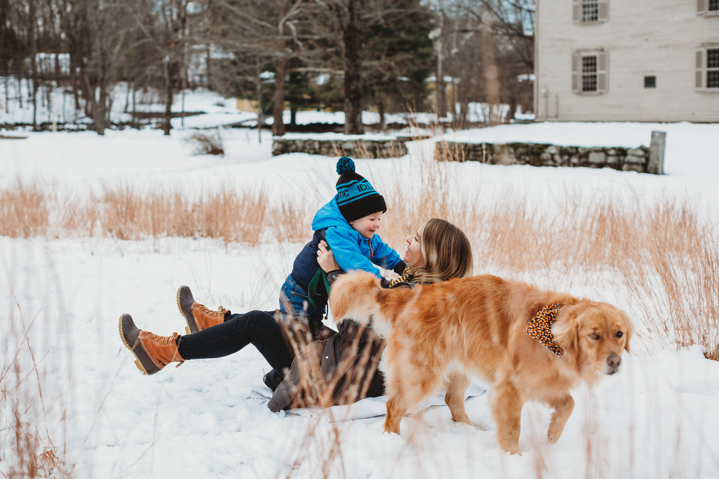 Mom and toddler playing in tall grass and snow. Minuteman Park / Concord family photographer.