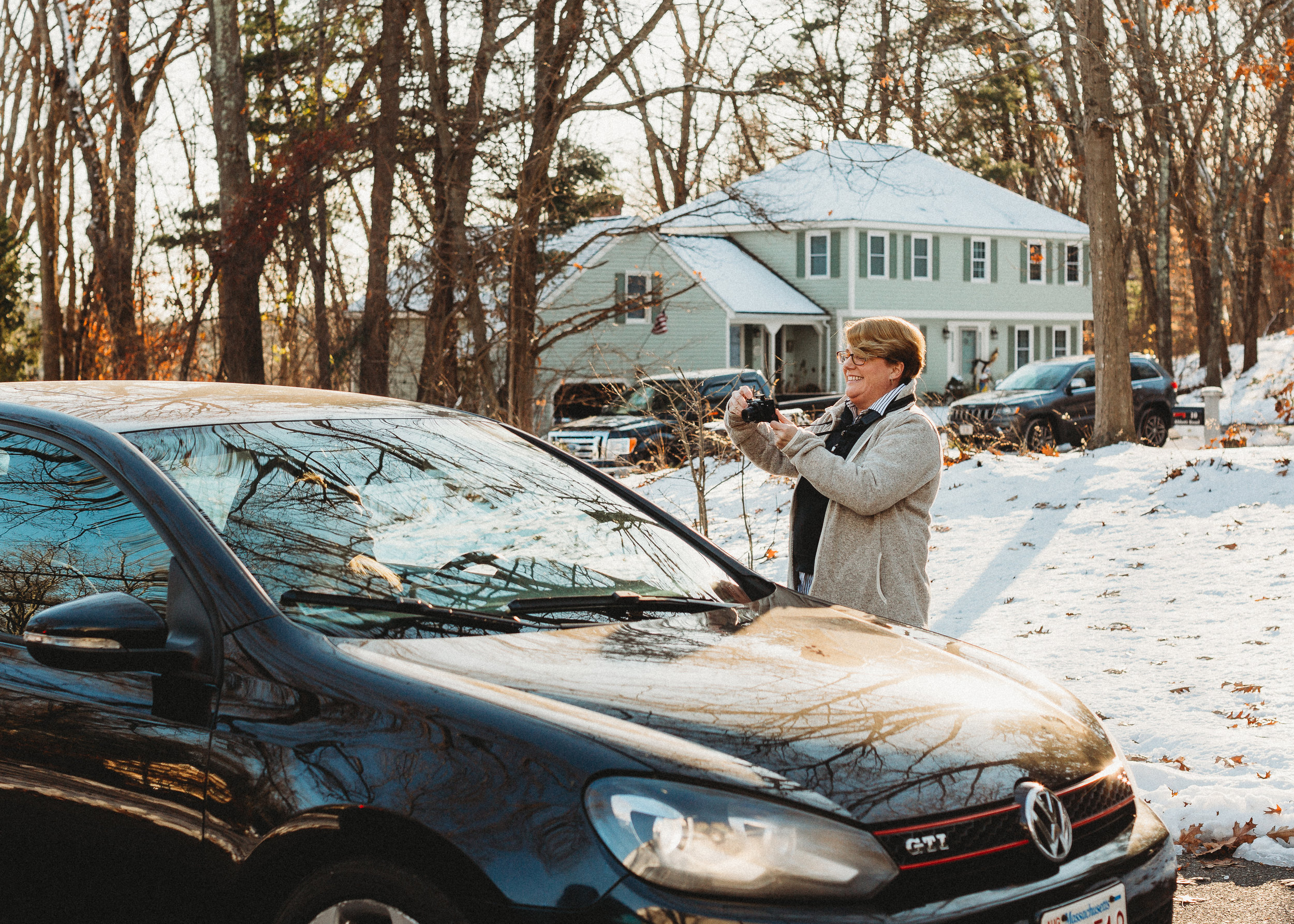 Mom taking a picture of daughter in new car. Sudbury family photographer / lifestyle photography / documentary photography