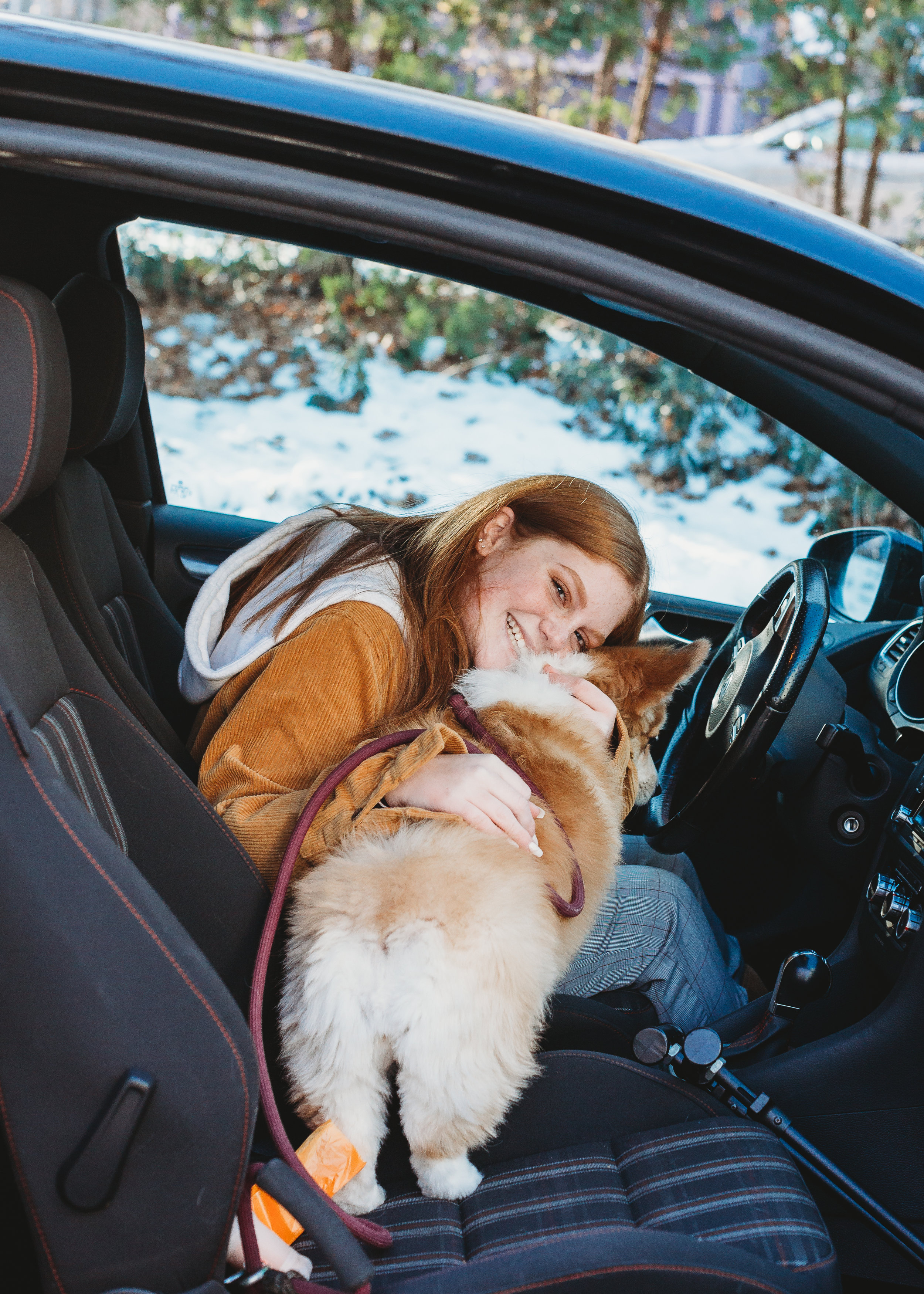 Our niece hugs our dog in her new car. Boston family photographer / lifestyle photography