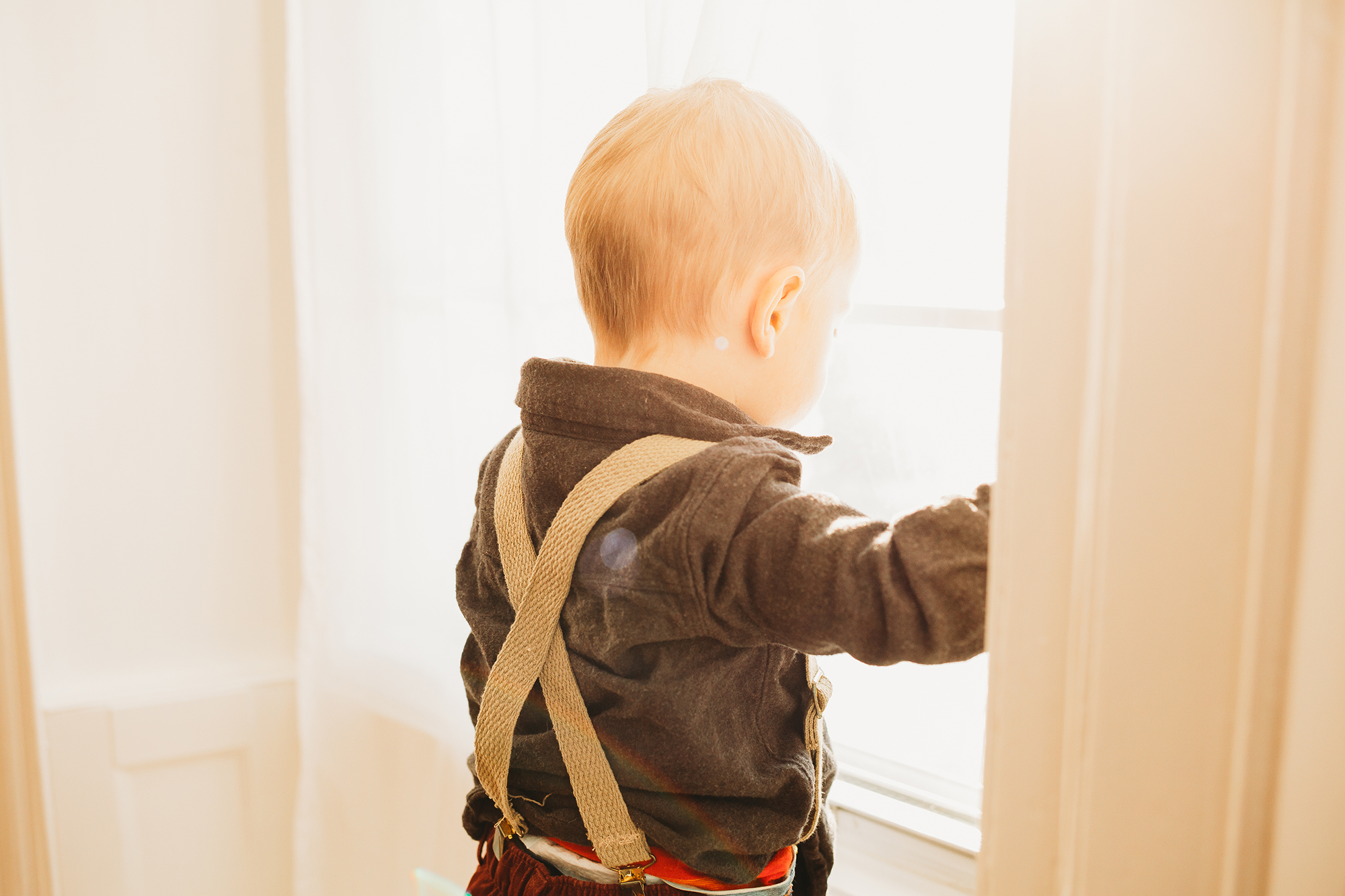Baby in suspenders looking out the window. What to wear babies toddlers. Family photography Boston.