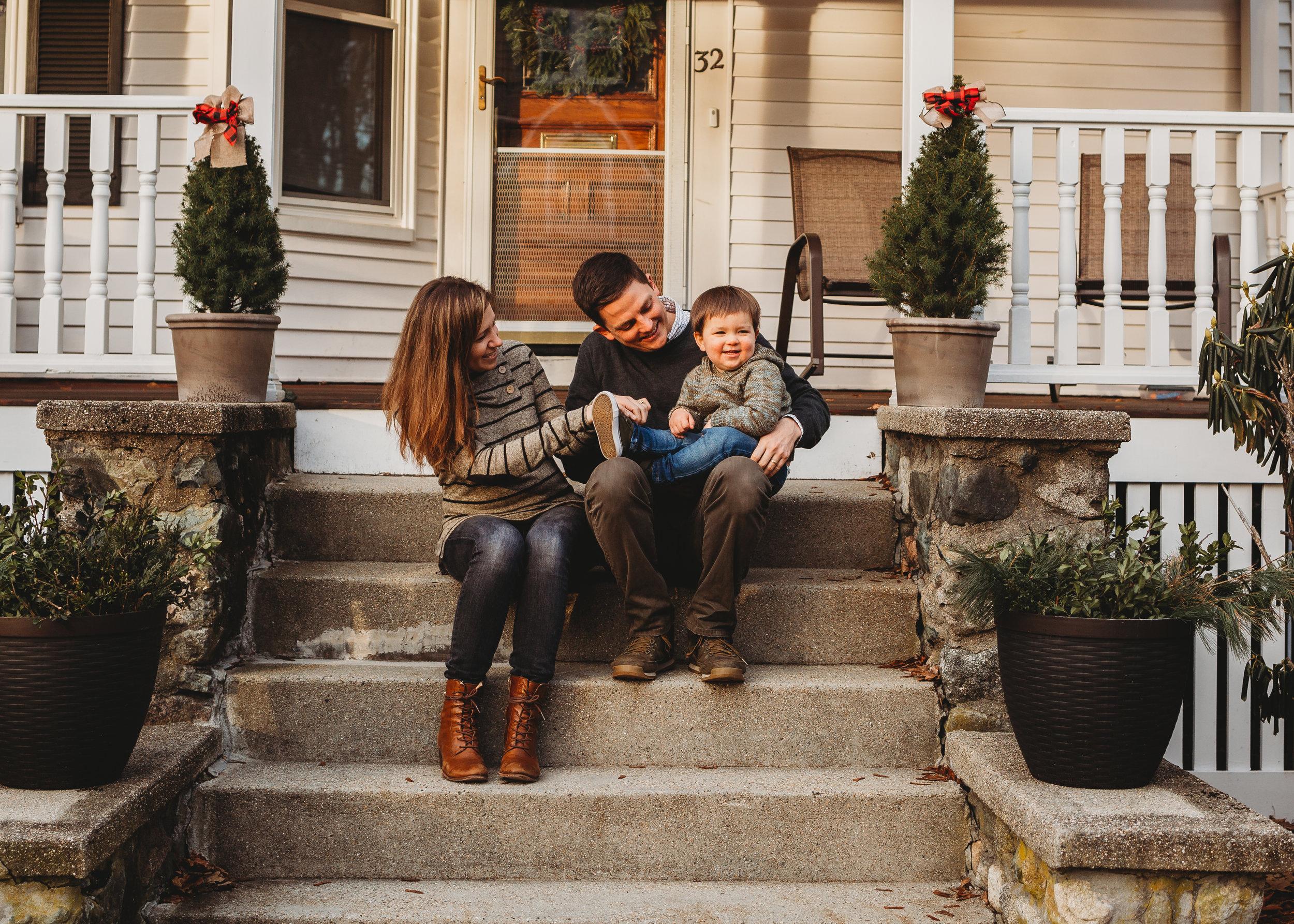 A Melrose, Massachusetts family sitting on the front steps of their home. Boston family photographer Joy LeDuc.