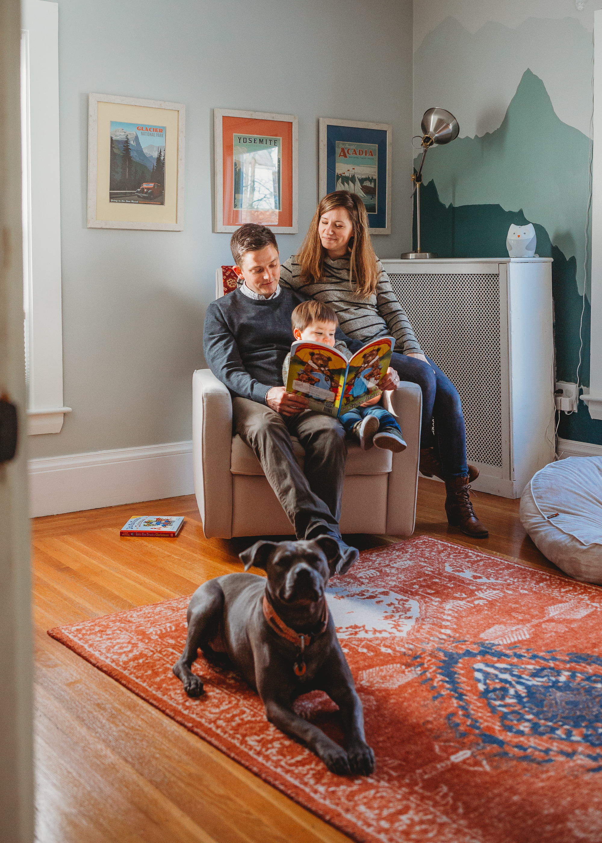 Mom, dad, toddler boy, and dog reading books in the nursery. In-home family photography in Melrose. Boston family photographer Joy LeDuc.