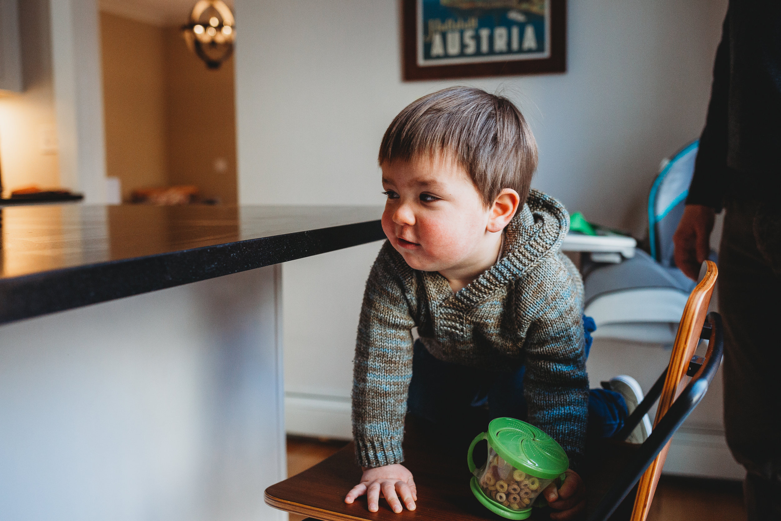 Toddler boy grabbing a snack during in-home lifestyle session. Boston family photographer Joy LeDuc.