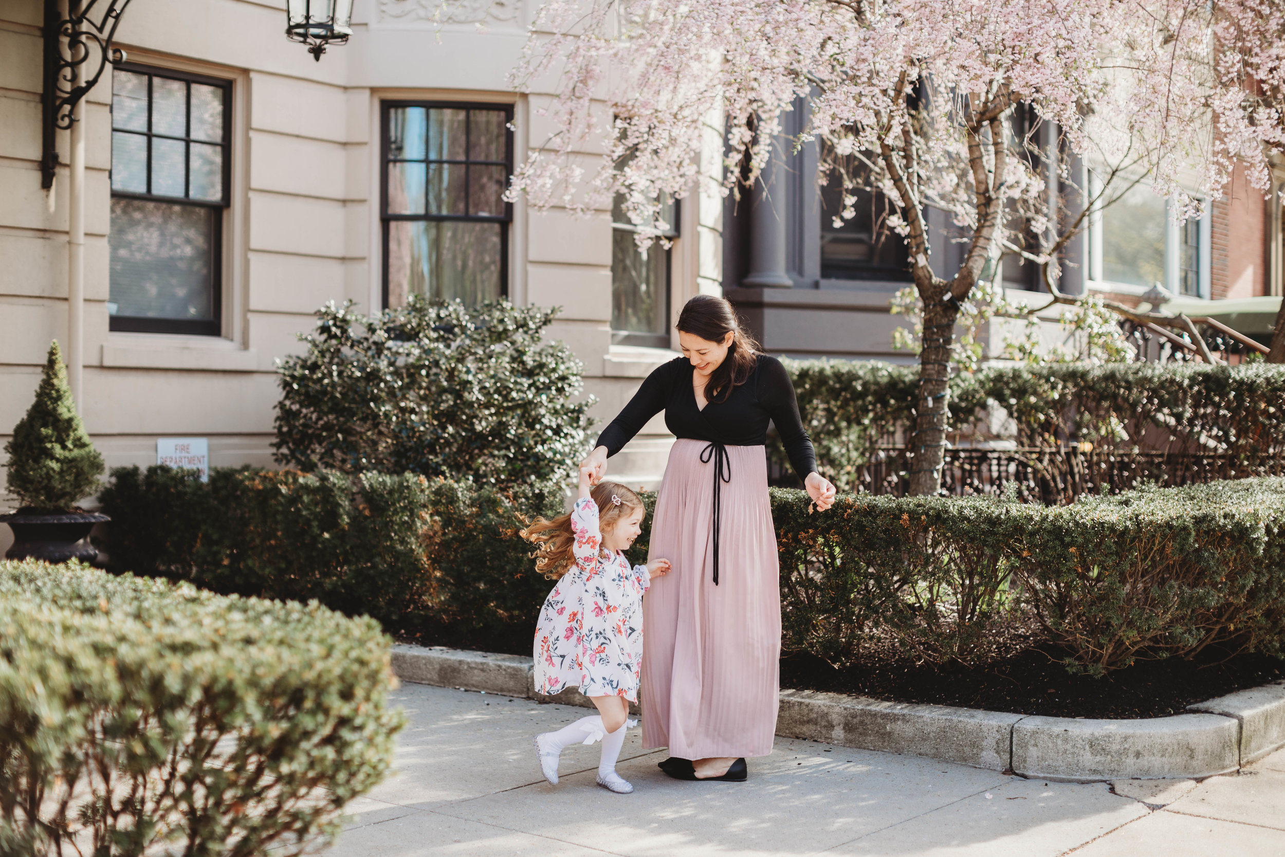 Spinning under the cherry blossoms in Back Bay. Boston family photographer. Mother daughter portraits. Lifestyle photographer New England.