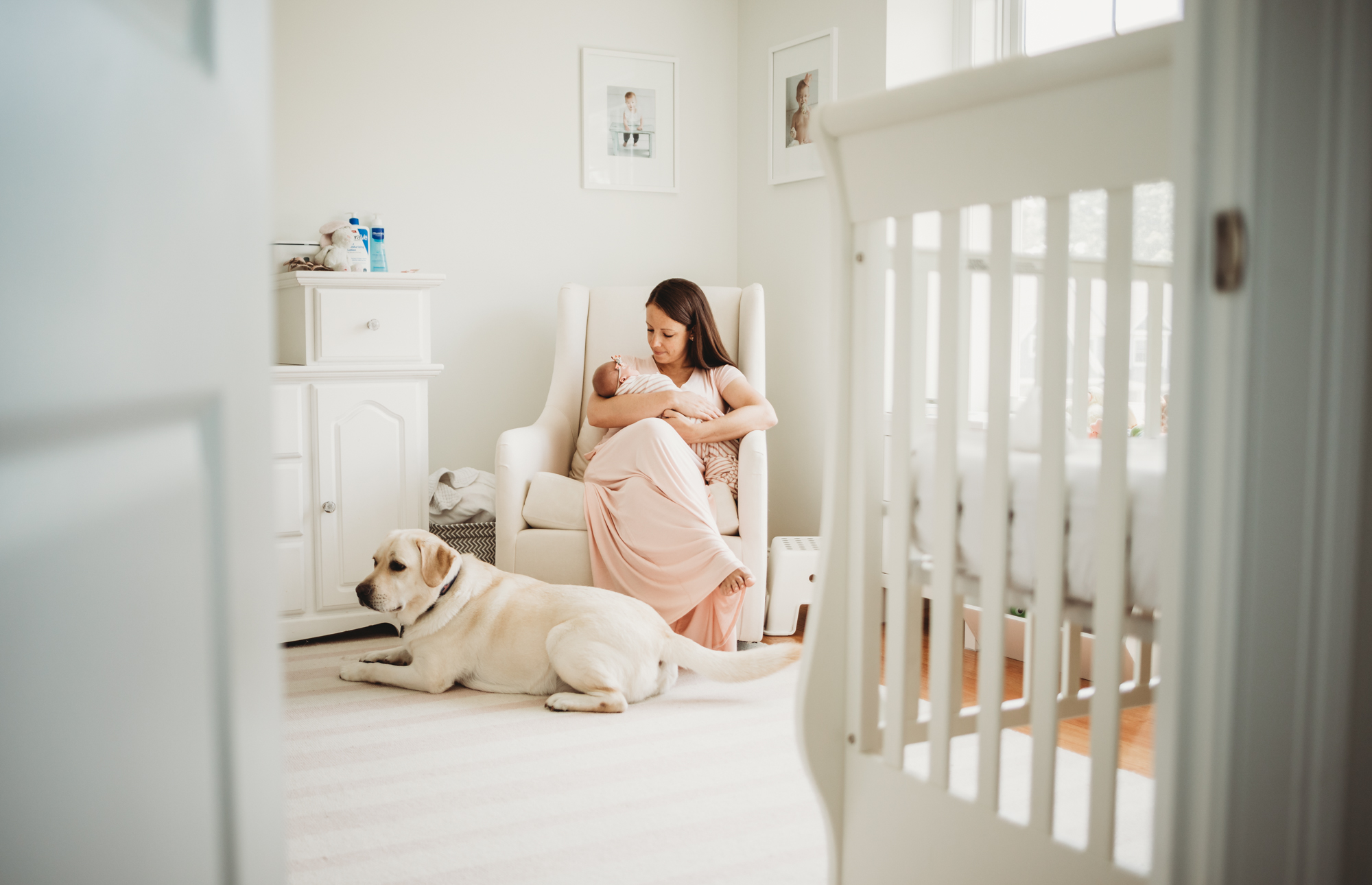 New mom in pale pink dress on rocker with newborn baby and white laborador on the floor at her feet. Wayland, Massachusetts newborn photographer in-home session. Lifestyle newborn photography in Greater Boston.