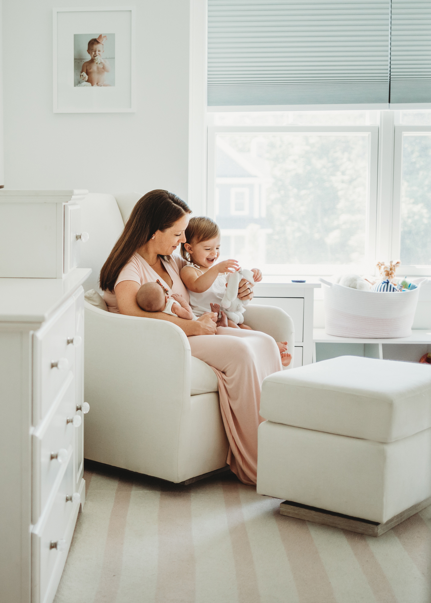 Mom with toddler daughter and newborn daughter in their nursery in Wayland, Massachusetts. Greater Boston newborn photographer. Natural light, lifestyle portraiture.