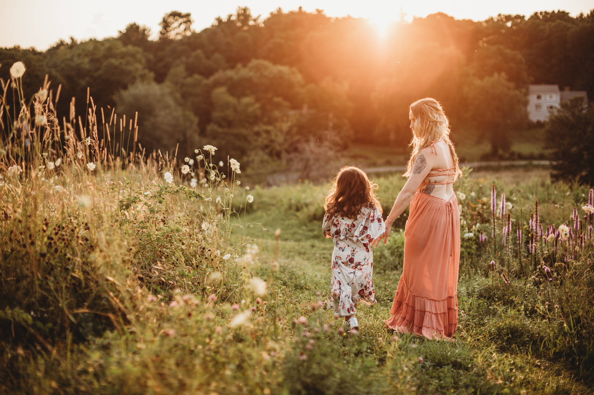 Beautiful mother and daughter walking down a Framingham, Massachusetts hill covered in wildflowers during their family portrait session in Greater Boston.