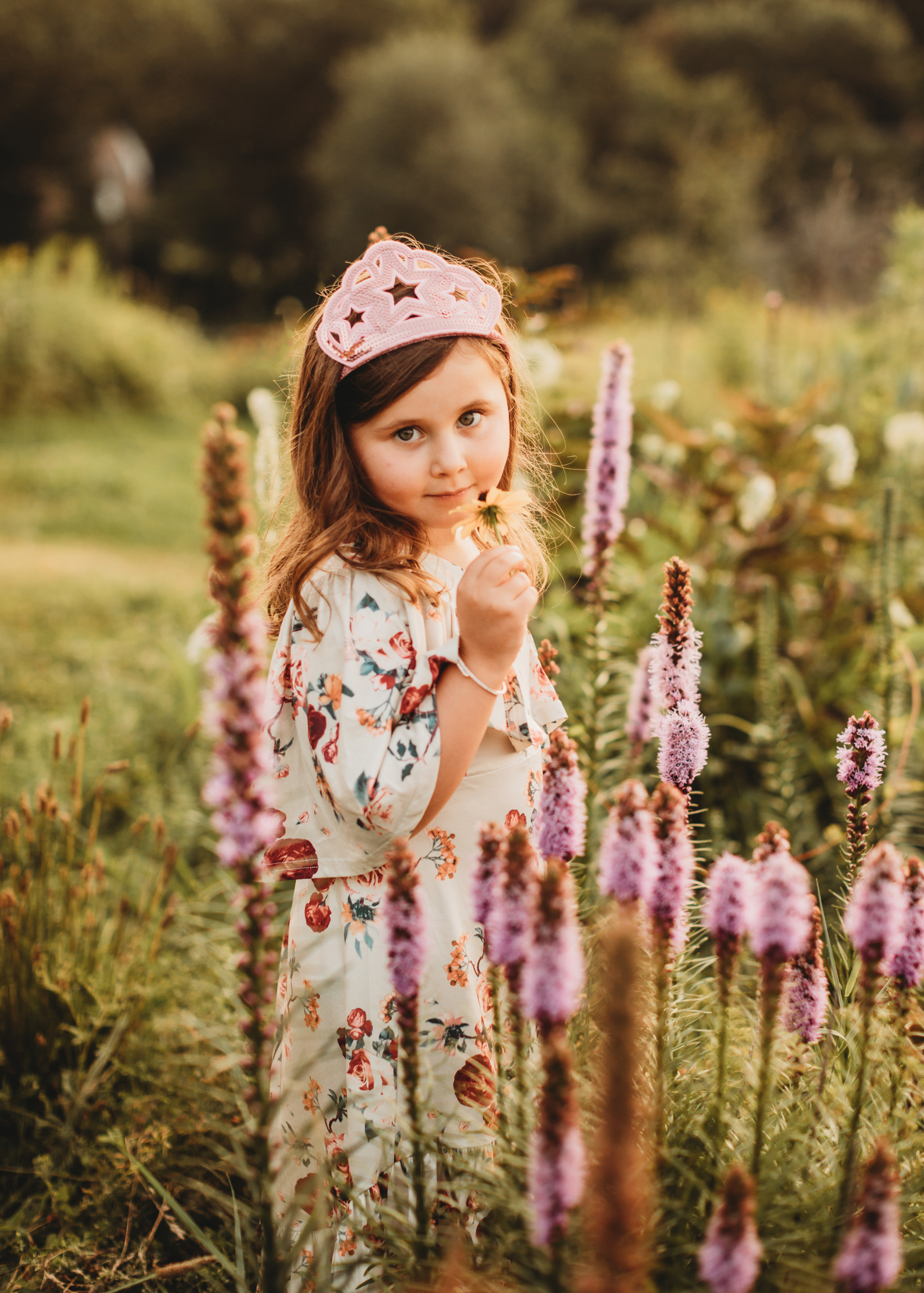 5-year-old Framingham, Massachusetts girl wearing her sequin crown while standing among the wildflowers (which are almost as tall as she is!). Photo by Greater Boston family photographer Joy LeDuc.