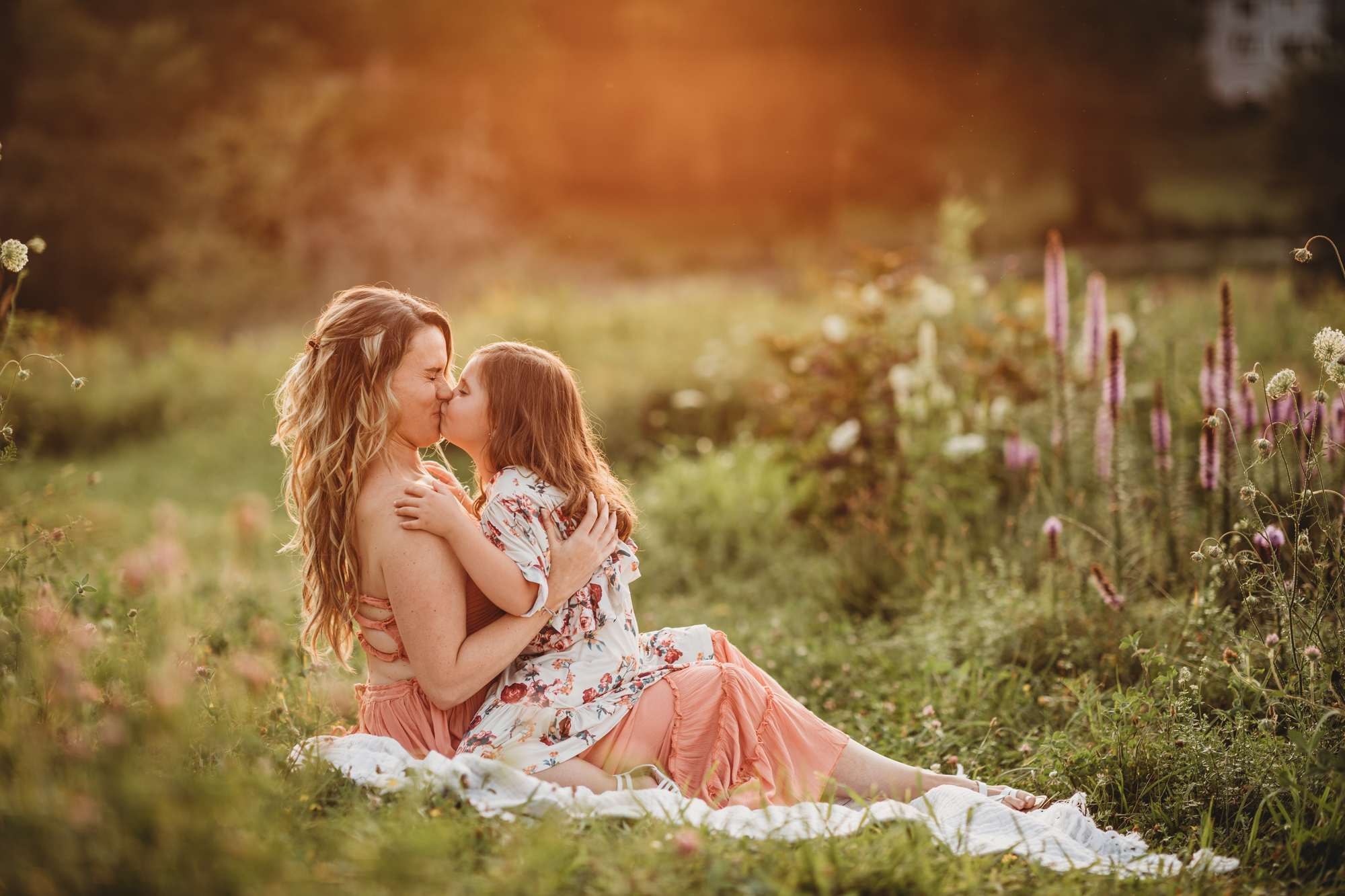 Mom laughing as daughter gives her a big kiss during their Framingham, Massachusetts family photography session. Golden hour in Greater Boston. Natural light lifestyle photography.