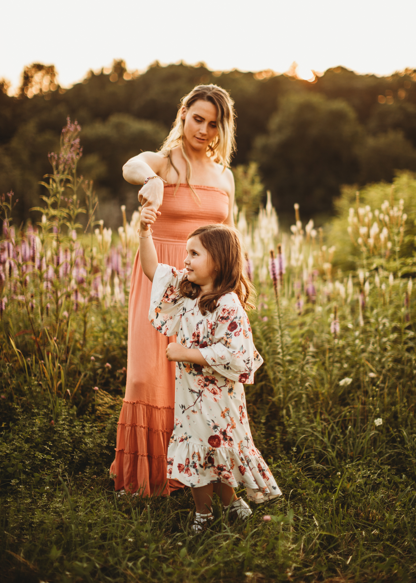 Mother in a long boho dress twirling five-year-old daughter during their sunset family portrait session in Framingham, MA. Greater Boston family photography. Summertime family photos.