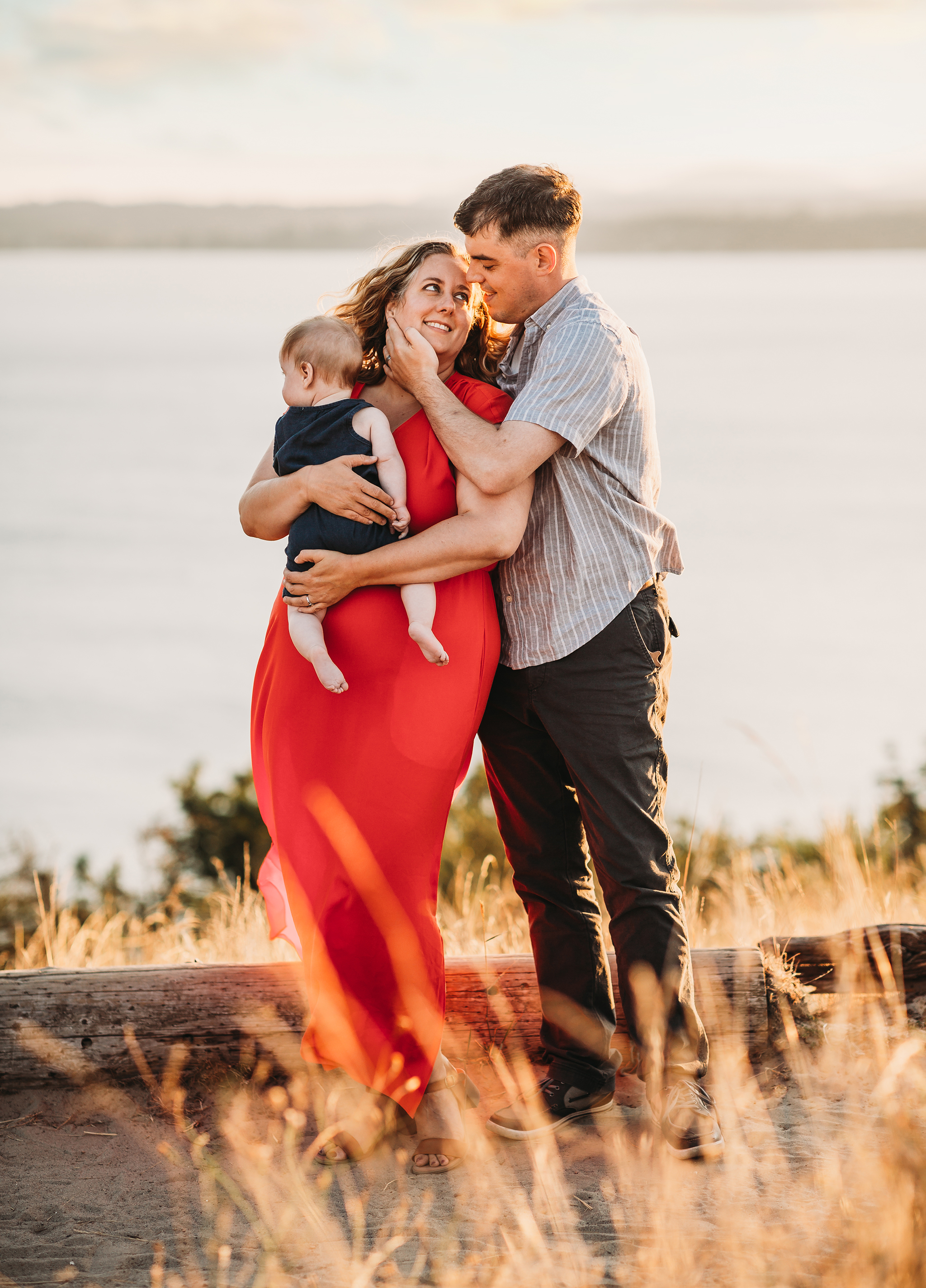 Step one to choosing what to wear for Boston family photos: start with mom. Photo of beautiful mom in red dress holding baby while husband touches the side of her face lovingly.