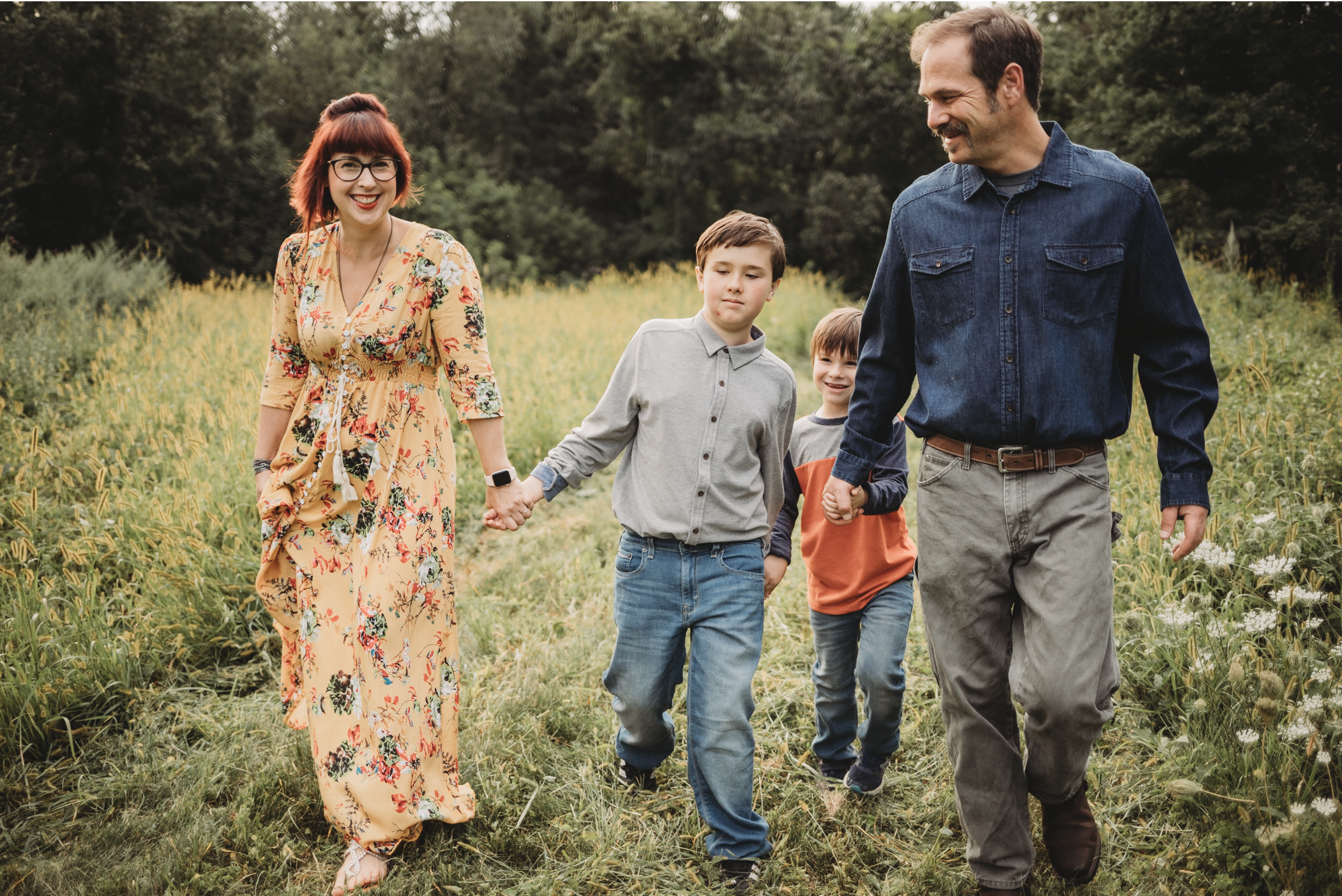 I always suggest starting with mom for family outfit planning! Photo of family walking in a field, with a beautiful mom wearing a long, flowy dress in sunshine yellow with a floral pattern.
