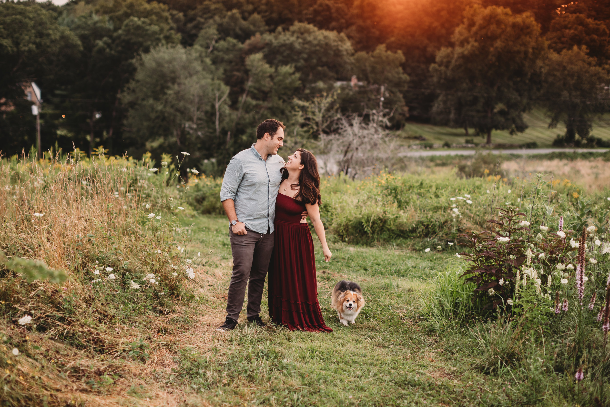 What to wear for family photos: start with mom. Client closet for Joy LeDuc Photography moms. Beautiful couple standing on a hill in Framingham, MA during golden hour with their fluffy corgi!