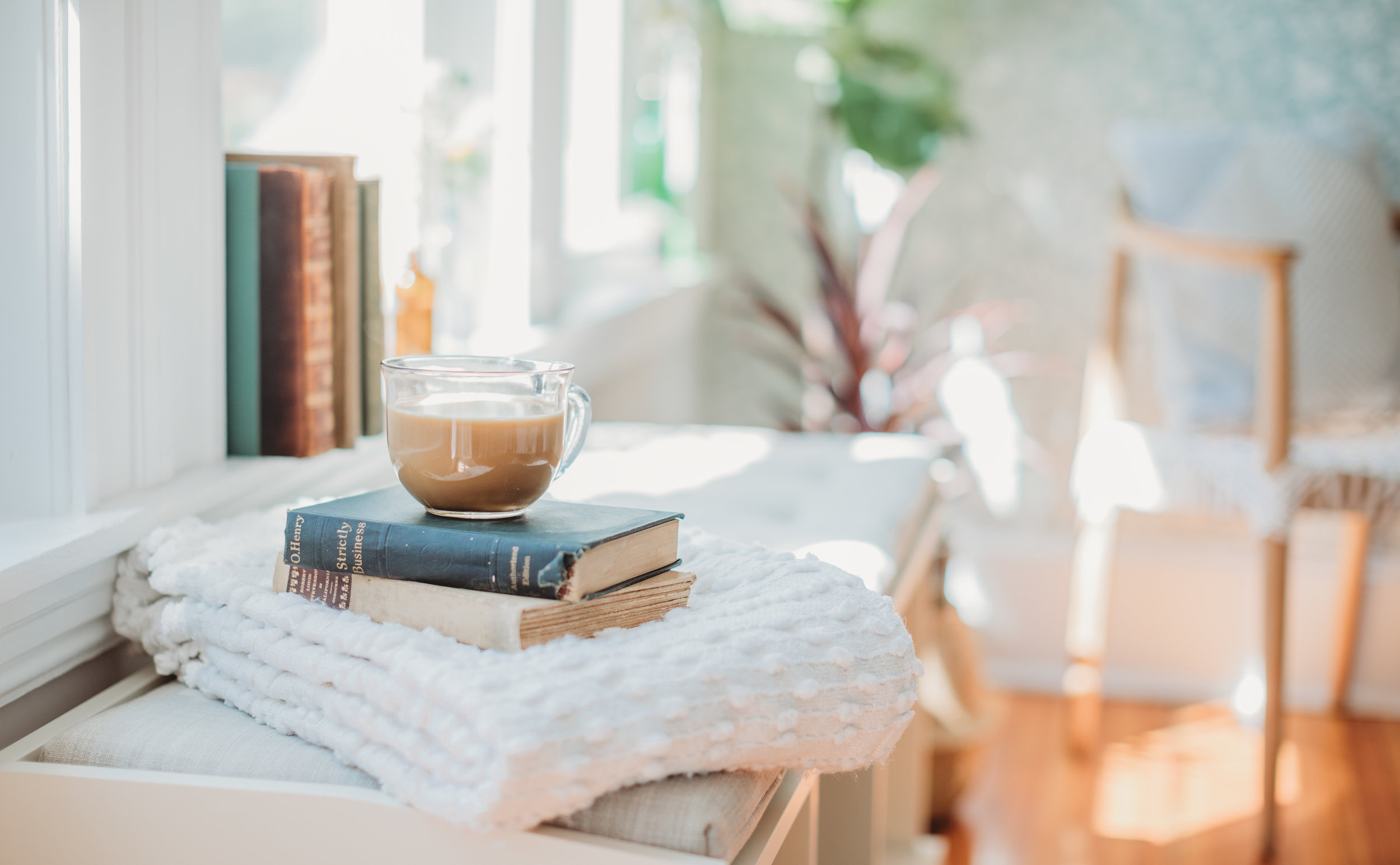 Coffee cup on a stack of books in a bright and sunny office. Boston branding photographer Joy LeDuc shares ideas on props to include in your personal branding photo session.