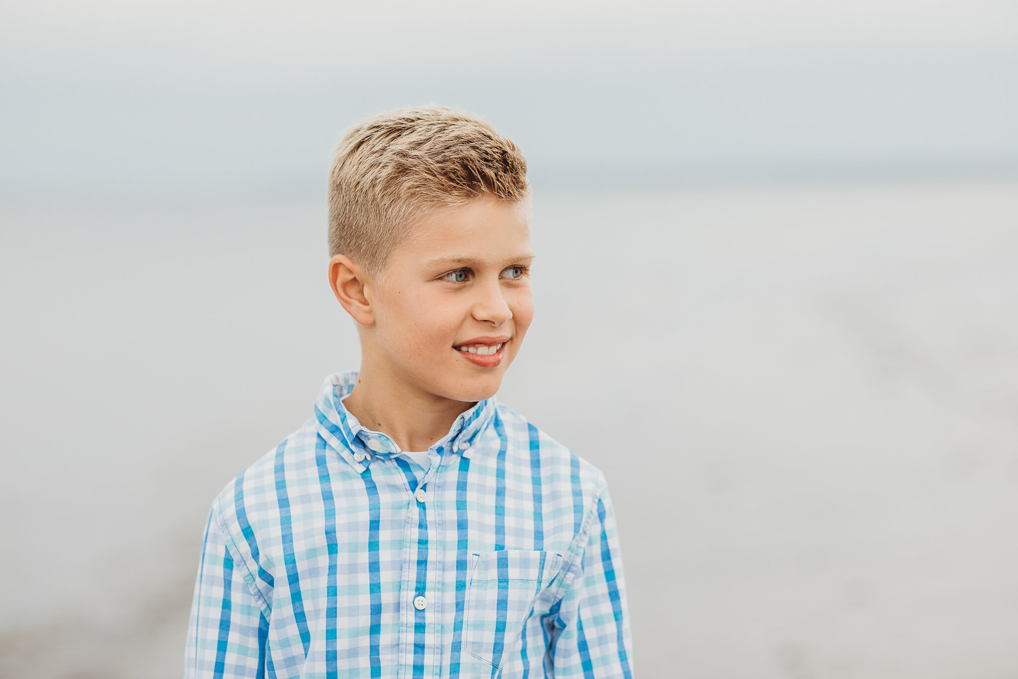 Little boy on the beach during his family's photo session on a stormy day in Greater Boston. Cloudy days don't ruin family photos—quite the contrary! Cloudy days make for some of the most beautiful family photos, with saturated colors and beautiful light.