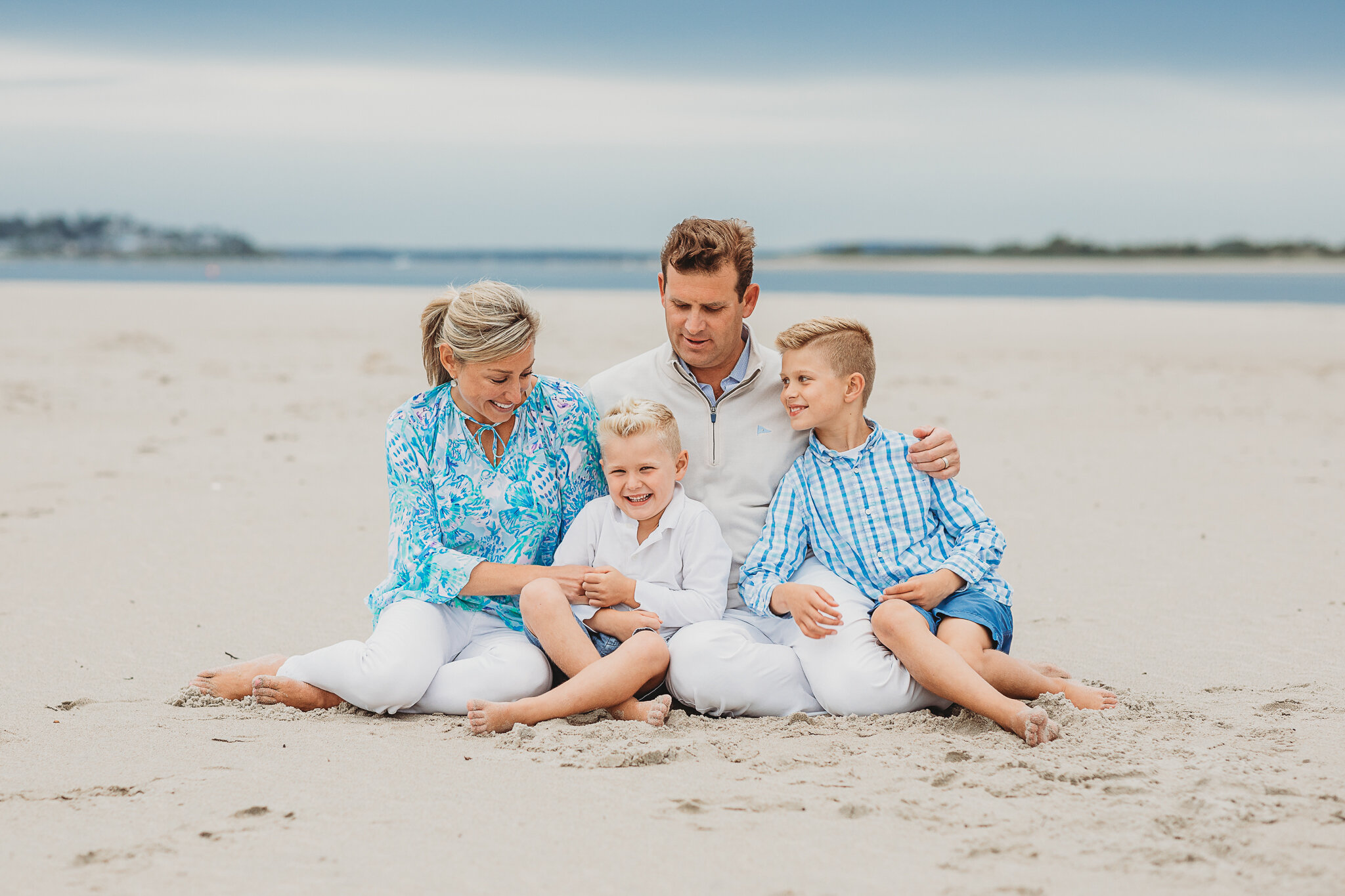 Beautiful Wellesley Boston family sitting at Crane Beach on a cloudy day in September. Cloudy days are just as beautiful as sunny days for family photos!