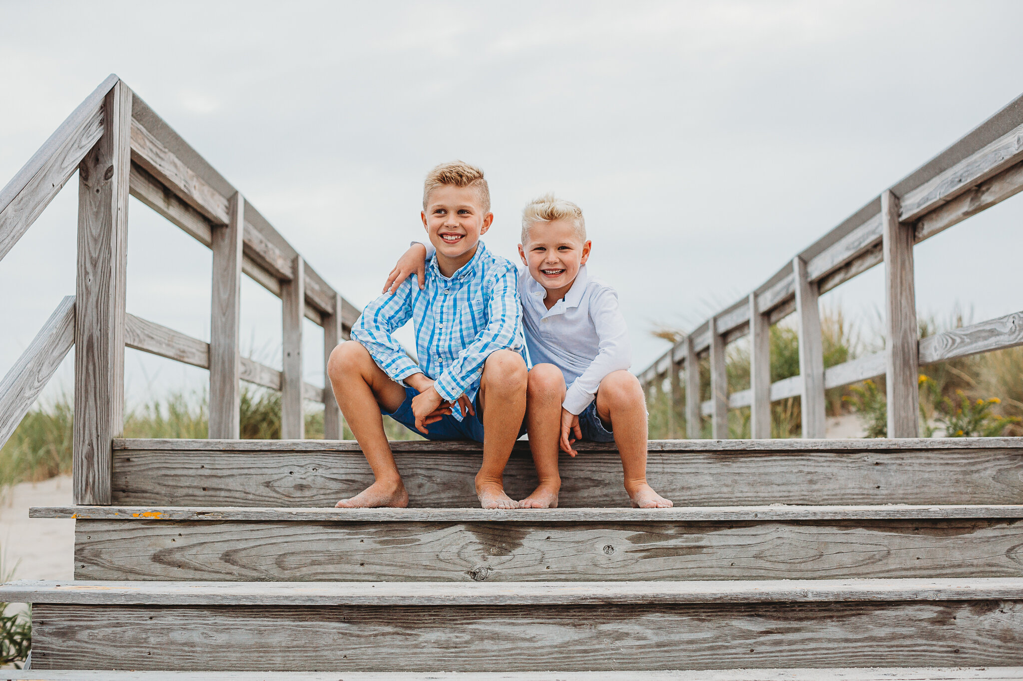 Brothers sitting on the boardwalk at Crane Beach. Cloudy days can be awesome for family photos in Greater Boston because you can face in any direction and capture beautiful photos! This image wouldn't have been possible on a sunny day.