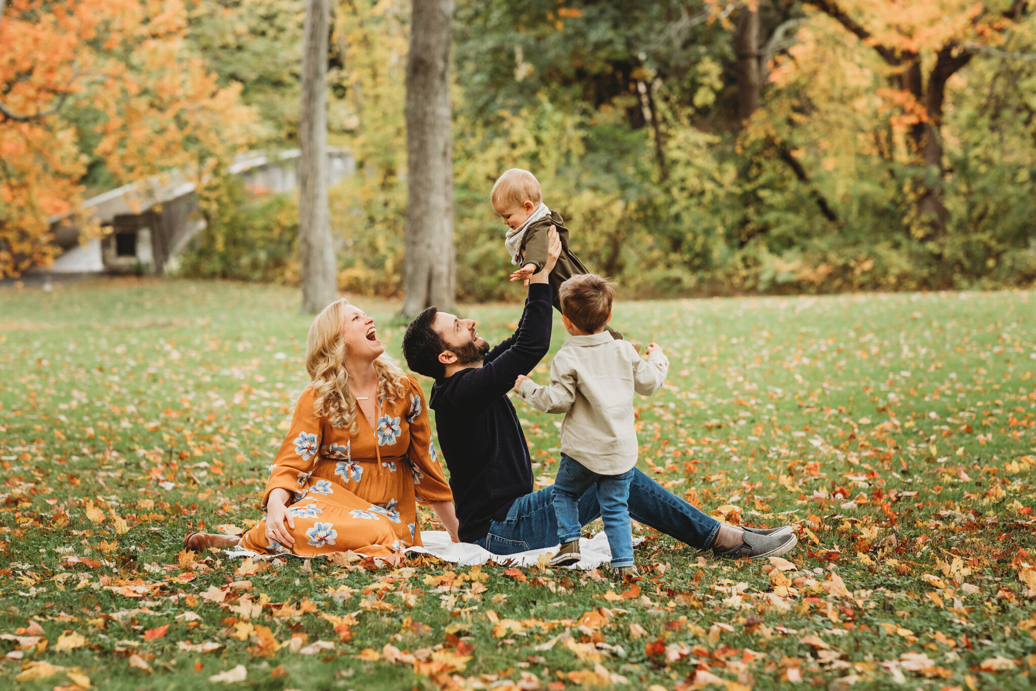 Family of four from Sudbury on a leaf covered lawn with bright foliage behind them during their family photo session. They booked almost a year ahead of time to score this prime foliage spot! Metrowest Boston families: how to score a fall foliage family photography session.