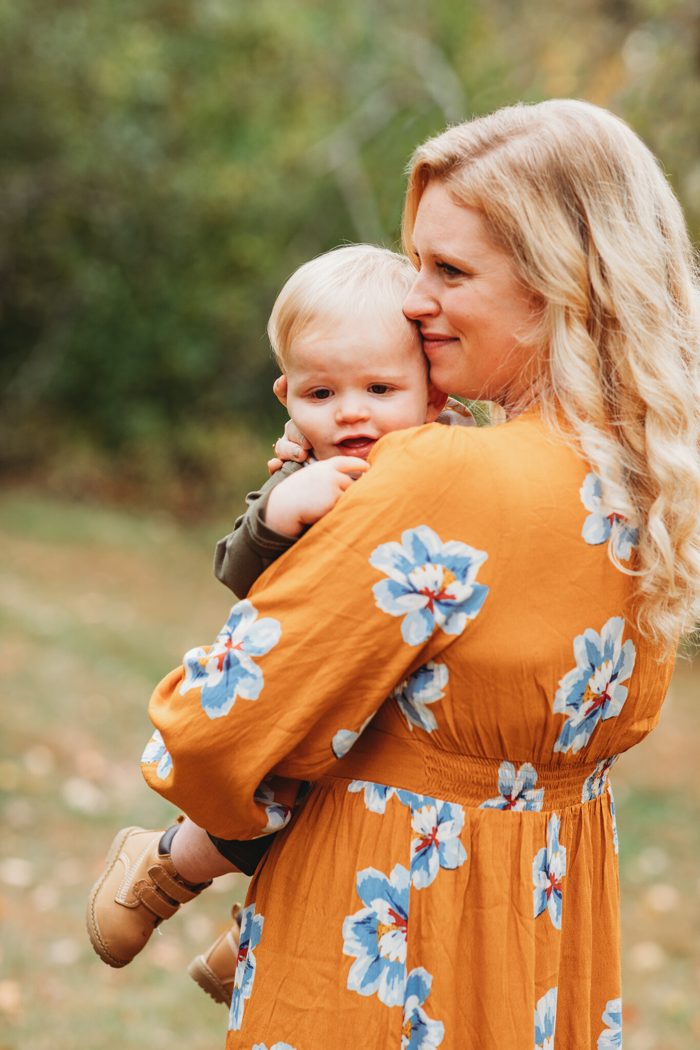 Beautiful Sudbury, Massachusetts mom wearing an orange dress and holding her one-year-old son during their fall family photography session. How to score a coveted autumn foliage photography session.