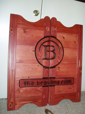 The Branding Room western saloon door with red stain and company logo
