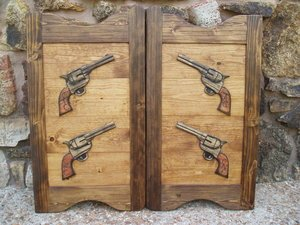 Western saloon door with carved six shooter pistols