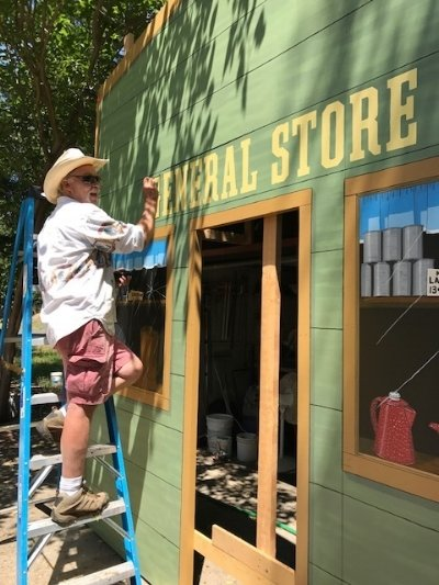 Owen at work hand painting a western town facade general store sign.