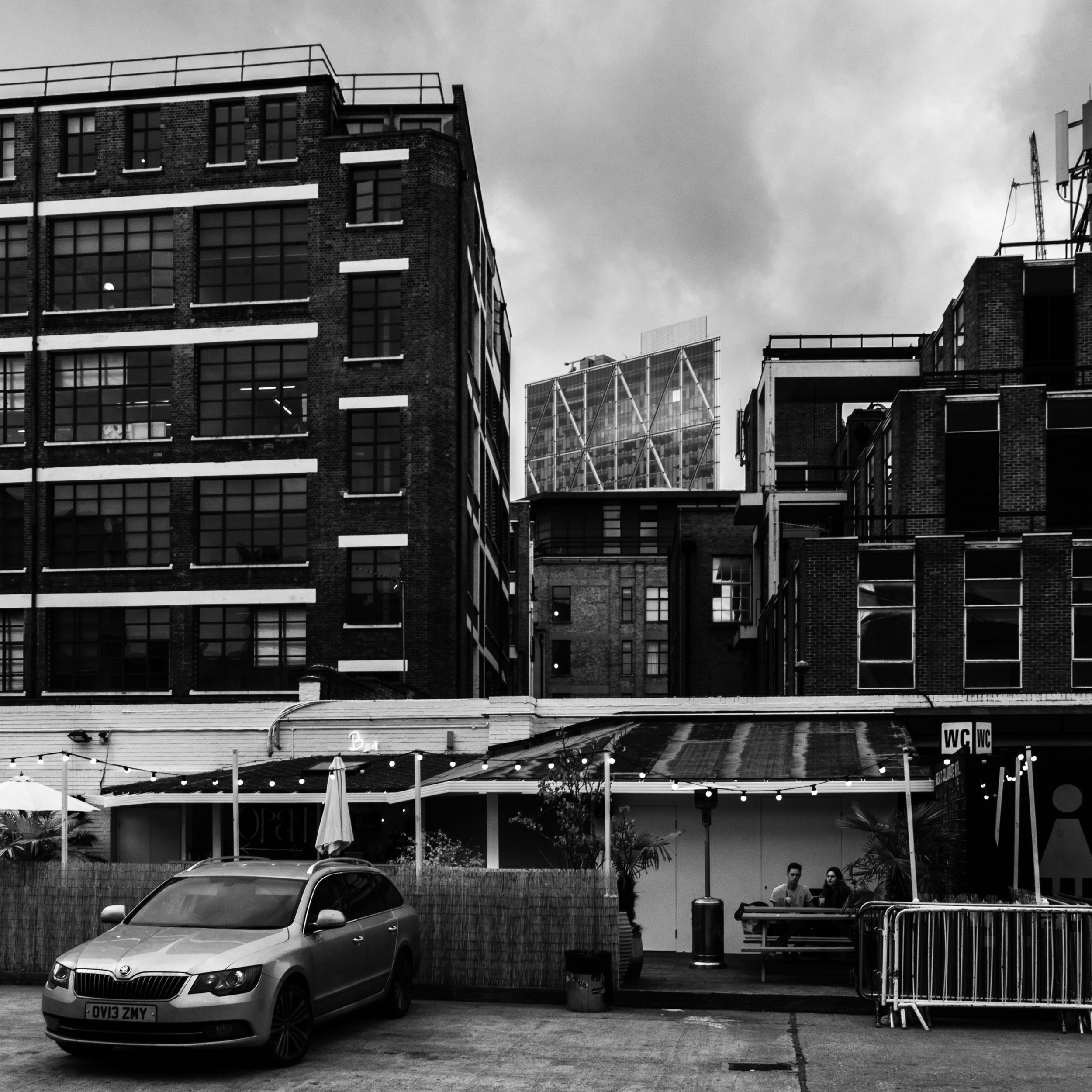 Broadgate peeping through the old blocks in the courtyard of the Old Truman Brewery