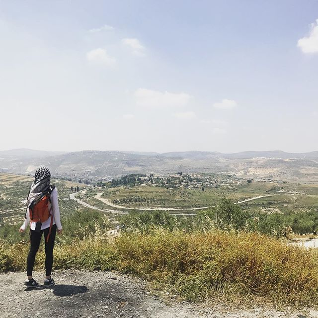"""Things are not always as they seem. 👀 On first glance, this might just appear to be a nice view. Let me tell you a bit more about it. 🌳 What looks like a village in the distance is an Israeli settlement in the West Bank. I'm standing on a hill in a town called Sebastia. It is home to significant religious sites + archeological ruins (some of which are just steps from where I stand). * What looks like a nice view is a highly contentious area. According to the Fourth Geneva Convention, occupying powers are prohibited from moving civilians into occupied territories. Which would render this settlement illegal. On the other side, Israel believes they rightfully captured this area in a defensive war and thus, according to that logic, the Geneva Convention doesn't apply. * The settlement in the distance is surrounded by barbed wire. Israeli people can exit and enter as they wish. Palestinian people are not allowed in. Israelis living in this settlement have 24/7 access to water. Palestinian people in the area I'm standing have restricted water access. * Parts of Sebastia - including some of the archeological ruins - are designated as """"Area C."""" Area C in the Palestinian Territories means Israeli control and security. Which also means that access, excavations, and restoration of archeological sites fall under Israeli control. * This area has a long and contentious history (and present) that cannot be fully understood in a single visit or explained in an IG post. I just want to encourage you to travel deeper, talk to local people, try to understand what may appear to be a nice view may also be an eyesore and more to someone living in the place you are passing through. * I also want to add that one of the reasons I stopped posting on IG was bcuz I was deeply impacted by my visit and then faced intimidation and interrogation by Israeli border officials when crossing back into Jordan. I wanted to share more from my trip but was afraid of what would happen if I did. Equally, I di"""