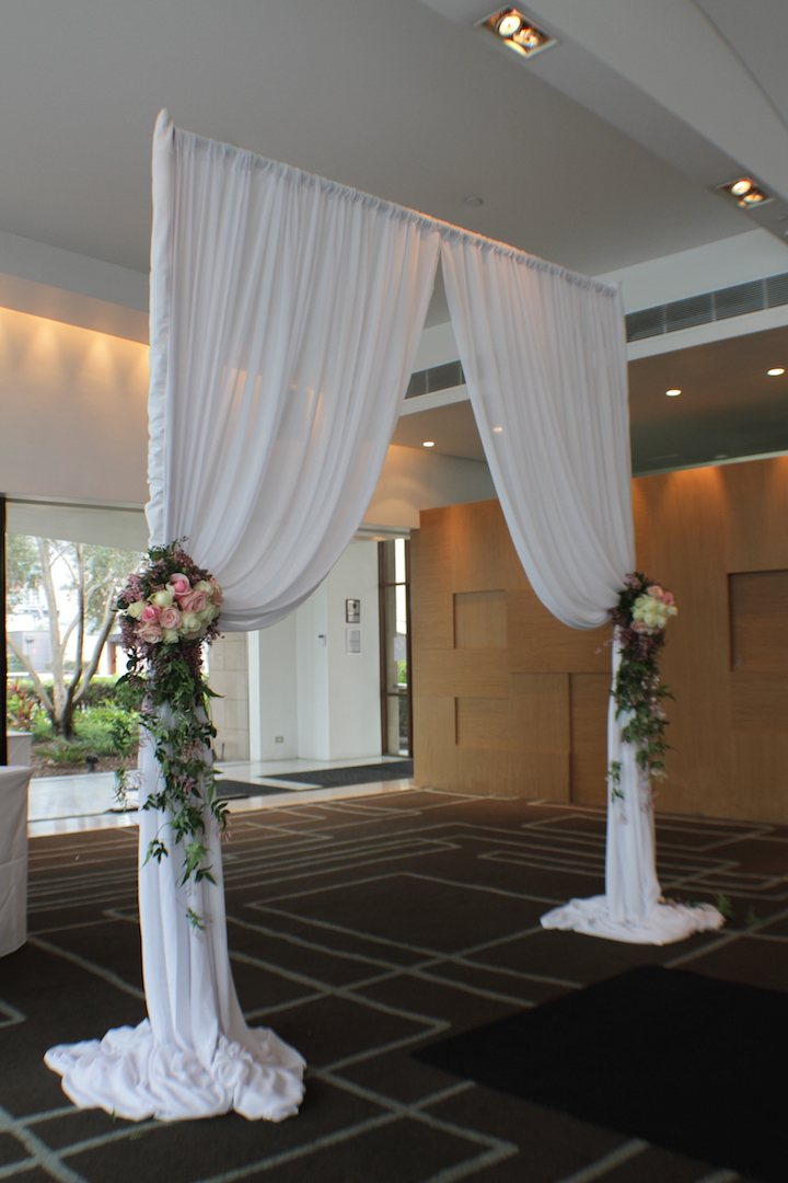 L'Aqua - Terrace Room - Ceremony - Half white chiffon canopy with an arrangement of seasonal fresh flowers on either side where fabric gathers.JPG
