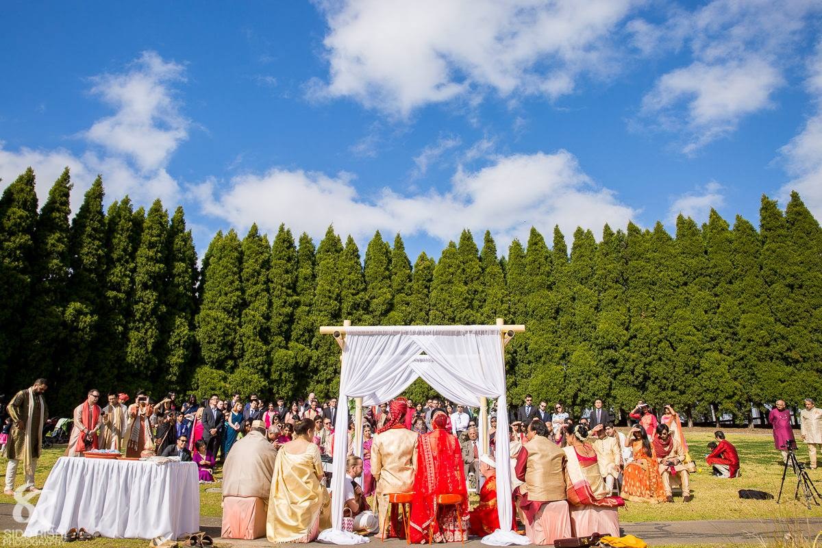 SOP - Arc of Pines - Ceremony consisting of white folding chairs and 4 post bamboo canopy with white chiffon. jpg.jpg
