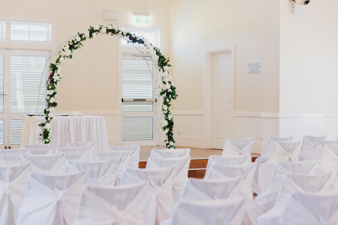 Breakfast Point - bridal arch with white tie back chair covers and signing table .jpg