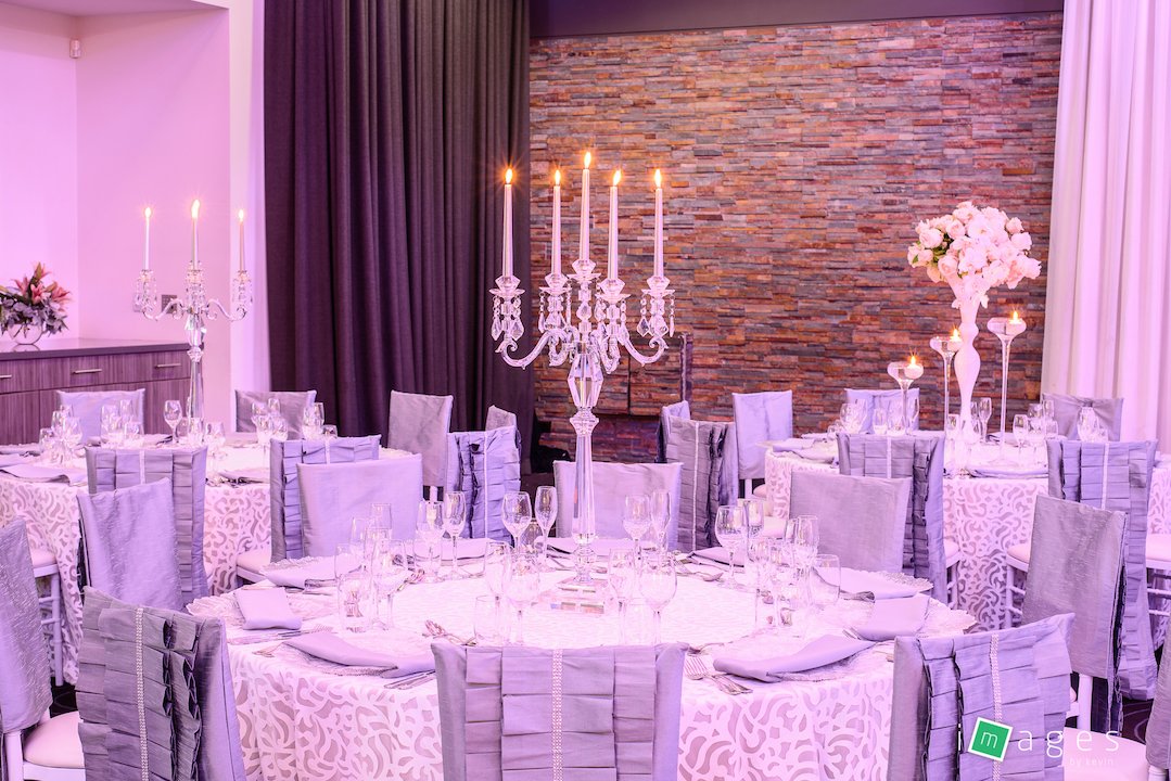 Waterview - Park Room - Guest table centrepiece consisting of medium crystal candelabra, PB White Lori chair caps and Fiori tablecloths, clear glass charger plate with silver napkin.jpg