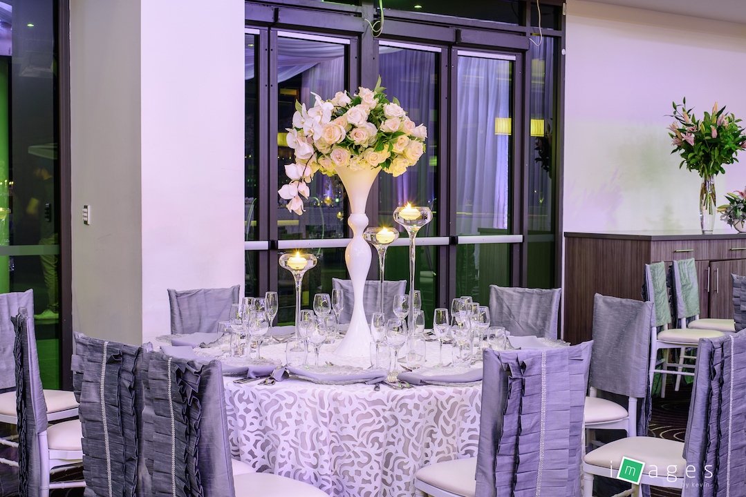 Waterview - Park Room - Guest table centrepiece consisting of white madonna vase with fresh florals and a set of 3 pavilion vases with floating candles, PB White Lori chair caps and Fiori tablecloths, clear glass charger plate with silver napkin.jpg
