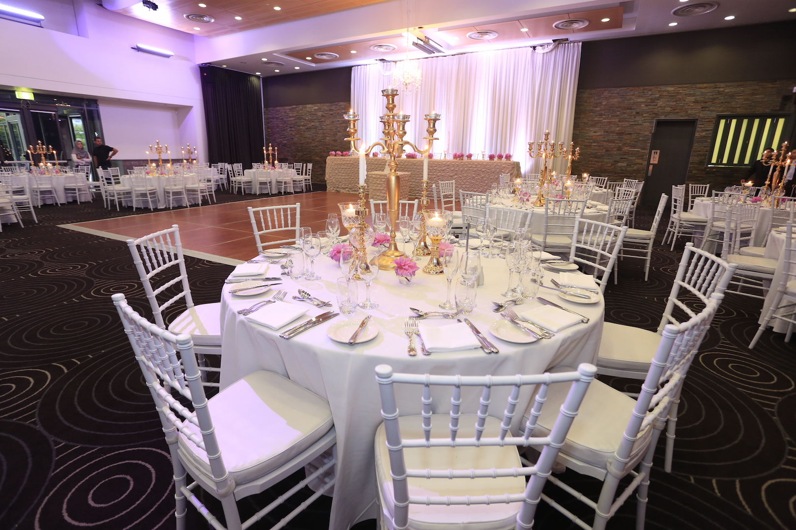 Waterview - Park Room - Guest table centrepiece - 5 arm gold candelabra with tea lights, gold candle sticks, gold goblets with floating candles, florals and white tiffany chairs - Image 3.JPG